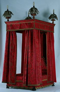 This bed typifies the expensive and sumptuous state beds installed in country houses in the late 17th century. Ralph Montagu, the first Duke of Buccleuch, acquired it for Boughton House, Northamptonshire, which he inherited in 1684. The bed was the centrepiece of the state bedroom, one of a series of rooms designed to show the wealth of the owner rather than for living in. The rich hangings are of crimson Italian silk damask brocaded with gold thread. They cover the oak frame entirely. The…