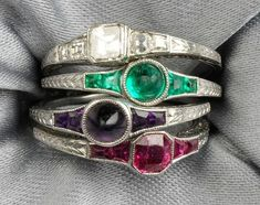 """Set of Four Art Deco Platinum Gem-set Acrostic Stacking Rings, T.B. Starr, set with a square-cut diamond, cabochon emerald, cabochon amethyst, and fancy-cut ruby, all with conforming shoulders, spelling out """"DEAR"""", engraved accents, approx. size 5 1/2, signed. At Skinner."""