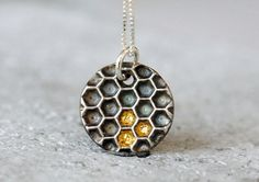 Silver honeycomb necklace with gold honey details.