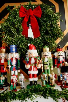 Nutcrackers in front of my living room mirror, arranged with a boxwood wreath and garland. #christmas