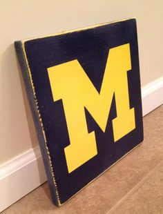 This is a wood wall sign measuring about 12 x 12. The sign has the U of M block M and is hand painted with navy background and bright yellow