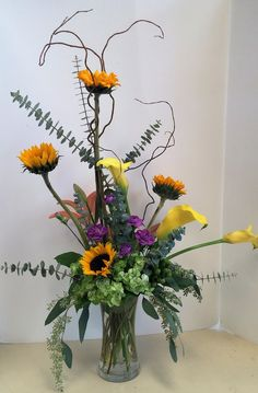 Fall arrangements, yellow calla lilies, sunflowers, sunset lilies, purple mini carnations, green hydrangea, curly willow, spiral eucalyptus, seeded eucalytpus