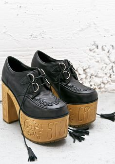 """Current Mood Steady Creepin' Platforms cuz yer the creep queen. These epic platform creepers will keep ya killin' da creep game with a super smooth vegan leather construction and badazz wooden platforms 'n heels that feature sik af carved doodles and read, """"steady creepin"""" across the front, complete with multiple D-rings, threaded details at yer toes and flogger lace closure with tassels."""