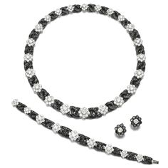 Diamond parure, Graff Comprising: a necklace composed of a graduated series of cluster motifs set with brilliant-cut diamonds, connected by curb linking set with brilliant-cut diamonds of black tint, length approximately 390mm; a bracelet, length approximately 175mm; and a pair of ear clips, hinged back fittings; each signed Graff, case stamped Graff.