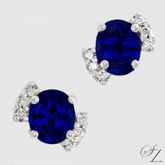 A spectacular, investment grade matched pair of Tanzanite ovals flanked by Diamonds. The intense blues of the Tanzanites are set off to great effect by the sparkling white of the Diamonds. A very unique and beautiful pair of earrings.