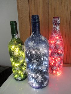 Christmas wine bottles.  Bottles used were colored glass, different colors can be found at Hobby Lobby.  A hole was drilled in lower backside for lights and Mod Podge, glitter and paper snowflakes decorate the outside.