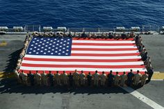 RED SEA (June 4, 2013) Sailors and Marines display the national ensign in honor of Independence Day aboard the amphibious assault ship USS Kearsarge (LHD 3). Kearsarge is the flagship for the Kearsarge Amphibious Ready Group and, with the embarked 26th Marine Expeditionary Unit (26th MEU), is deployed in support of maritime security operations and theater security cooperation efforts in the U.S. 5th Fleet area of responsibility.