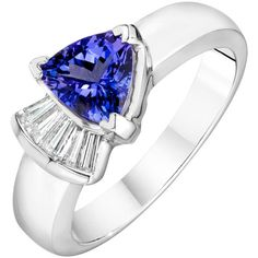 A modern design showcases a trillion-cut tanzanite (1.06 ctw), flanked by a row of baguette-cut diamonds (.20 ctw), set in a pristine 14k white gold band.