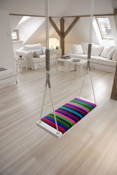 Neutral rustic look with the only color in the swing. Swings indoors seem to be rather popular