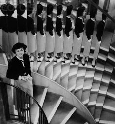 Coco Chanel, on the mirrored staircase of her couture house, March 1, 1954. Photographed by Suzy Parker.