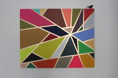 Put masking tape on a canvas, paint in between all the triangles/random geometric sections