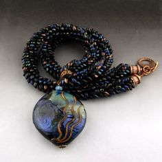 Blacks, blues, flashes of gold and bronze. Shiny and matte. All braided together to create a smooth dragon scale necklace. The lentil is decorated