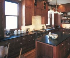 Red Wood Cabinets And Black Countertops