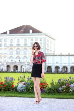 BY CHILL Chloe Hill at Nymphenburg Palace in Munich, germany; wearing mango palm print shirt, asos denim skirt, tomo ford sunglasses and tabitha simmons shoes