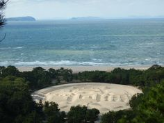 """17th century-style coin made of sand in Kotohiki Park. The park is adjacent to Temples 68 (Jinnein) and Temple 69 (Kannonji). The """"sand coin"""" is known as Kan-ei-tsuho in Japanese. It is said that viewing the coin will bring good health, long life and freedom from financial worry. Have a good long look!"""