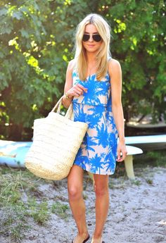 Katarzyna Tusk is wearing a blue and white palm print dress from River Island, sunglasses from Mango