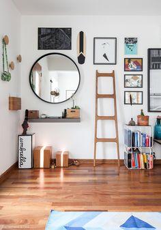 Hall de entrada tem espelho redondo, ganchos de madeira e  acessórios de madeira para organizar.