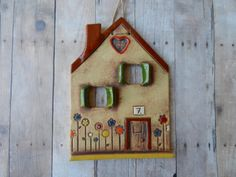 This cute house was hand build out of slab of clay. While the clay was still wet I have cut out the windows and added the door and all the little details. I have used iron oxide wash to highlight the texture of the house. It is glazed with colorful glazes. I have attached a hemp string for easy hanging on the wall. It will make a nice gift to somebodys new home. Measurements: approx. H 5 1/2 x W 4 All my hand build pottery has its own personality and imperfections, which makes it a t...