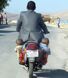 This father travels on a rickety-looking bike with his two children attached to the back... and neither are wearing helmets