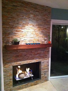 Slate fireplace w/ linear stacked stone for a modern feel.  Geoshapes replace traditional fire logs.