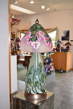 Daniel Lotton Art Glass and Lighting - Very unique one of a kind lamp with cascading pink Iris's, The leaves swirl with greens and golds and the stems twirl. Finished elegantly with custom fitted bronze lamp parts.