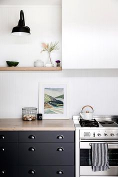 simple, modern kitchen, black cabinets, floating shelves, bin pulls, barn light wall sconce