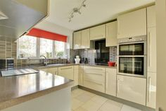 Modern fitted #kitchen with a range of wall and base cupboards with work surfaces over. Integrated double oven, microwave, dishwasher and fridge. Four ring electric hob. Extractor fan. Underfloor heating.