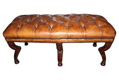 Stunning custom tufted leather bench with unusual carved animal legs and double nailhead trim.