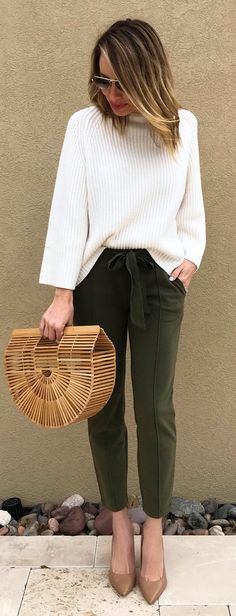 #spring #outfits  woman in white sweater and green pants holding brown handbag while standing near brown painted wall. Pic by @jaimeshrayber