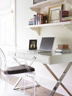 Modern office design with Phillipe Stark Louis Ghost Chair with black cushion, Jonathan Adler white Channing desk and white shelves.