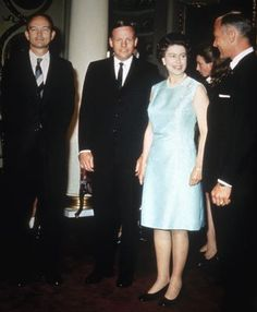 The Queen sent a message of congratulations to Apollo 11 astronauts for the first moon landing on July 21, 1969. The message was microfilmed and deposited on the moon in a metal container. Here she is meeting the Apollo 11 Astronauts after their trip to the moon in 1969 - an ice-blue satin cocktail dress ensures that she is seen against the black of their suits...