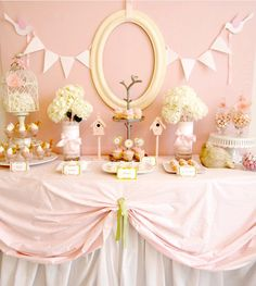 Pink themed baby shower with little bird theme - love the little bird houses next to the centrepieces and the cages with the hydrangeas add a real vintage theme.