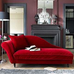 red recamier for living room decorating with fireplace, large wall mirror and crystal chandelier