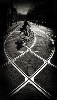Classic tram tracks black and white photo with silhouette of bicycle and rider.