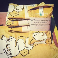 by boygirlparty on instagram: http://ift.tt/1QnGCYp -- restocking these yellow kitty onesies and other buyolympia/boygirlparty baby clothing in the shop as soon as I'm done folding! #boygirlparty #onesies #buyolympia #organiccotton #babyclothes #babyclothing #etsy