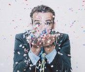 Un homme qui souffle des confettis multicolores.
