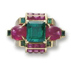 AN EMERALD, RUBY AND GOLD RING   Of geometric design, centering upon a rectangular-cut emerald, weighing approximately 4.56 carats, flanked on either side by a cabochon ruby, enhanced by rows of calibré-cut rubies and six bezel-set rectangular emeralds, mounted in gold