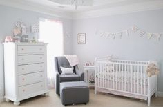 Unisex baby room. Light grey walls and white furniture