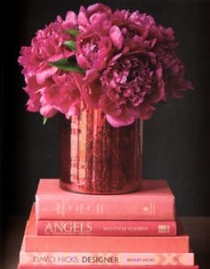 Hot pink and lovely flower arrangement on a stack of pink hued books.