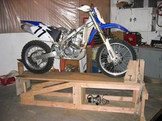 Motorcycle Lift - Homemade motorcycle lift constructed from wood. Features two positions: sloped, to facilitate mounting the motorcycle on the lift, and flat, to serve as a work surface after pivoting. Motorcycle Lift Table, Motorcycle Ramp, Bike Lift, Motorcycle Workshop, Motorcycle Wheels, Simson Moped, Homemade Motorcycle, Bike Repair Stand, Garage Shop