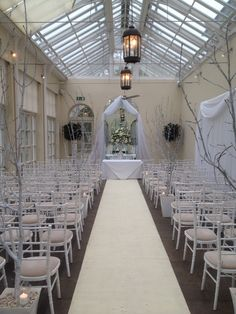 White chiavari chairs,aisle runner, mirror draping, floral garden urn, silver trees - orangery Buxted park - sussex wedding venue decorations