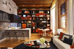 Exposed brick, great wall shelving and dark colors in this room