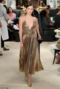 1f2e33afa9f1 Bella Hadid takes the plunge in metallic gold gown at NYC fashion show