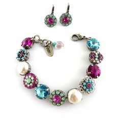 If youre a Southwestern kind of gal, this Swarovski crystal bracelet is for you! The combination of turquoise and opal flower embellishments, sparkly fuchsia and blue crystals accented with silky pearls makes this bracelet a stand out piece that will add a pop of color and flair to your every day casual attire or formal evening wear. The crystals are set in an antique silver plated chain. The Siggy tag and heart charm on the end complete the look.  ♡ genuine 12mm Swarovski elements ♡ Five…