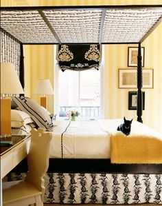 Domino yellow, black and white bedroom--canopy bed, patterned bed skirt, relaxed roman shade, striped walls