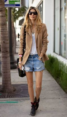 Go for a khaki wool blazer and light blue denim shorts for a casual level of dress. A pair of black leather boots brings the dressed-down touch to the ensemble.   Shop this look on Lookastic: https://lookastic.com/women/looks/blazer-v-neck-t-shirt-shorts/19043   — Dark Brown Sunglasses  — Tan Wool Blazer  — White V-neck T-shirt  — Gold Bracelet  — Gold Watch  — Light Blue Denim Shorts  — Black Canvas Crossbody Bag  — Black Leather Boots