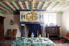 The vivid colors of the coffered ceiling and the chimneypiece animate the dining room in William Christie's French countryside estate. The table is covered in a Prelle silk.
