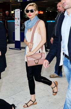 Sienna Miller pairs a silk tank, light blue scarf, flat sandals with sleek cropped black pants and a blush pink bag