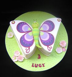 a purple and pink butterfly cake. Lemon syrup cake with raspberry Neoclassic butter cream covered in white chocolate ganache under fondant.