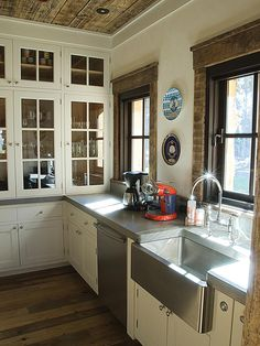 This adorable country kitchen features a tongue-and-groove wood ceiling and rough-hewn window trim. Granite countertops, a stainless-steel farmhouse sink and white glass-front cabinets make it a fun and functional place to cook.